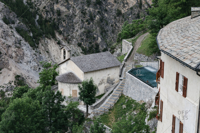 Bormio, Italy - June 26, 2017: Outdoor thermal swimming pool and buildings at historic resort in the Italian Alps