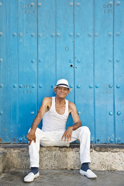 Senior man in all white and a Panama hat sitting in front of a teal building
