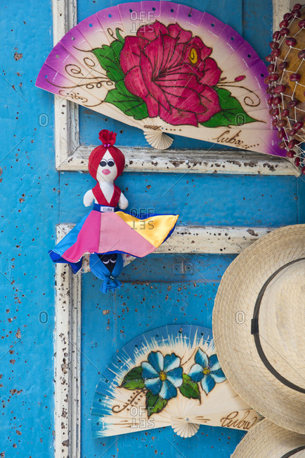 Havana, Cuba - May 23, 2017: Colorful fans and a doll on a peeling blue door