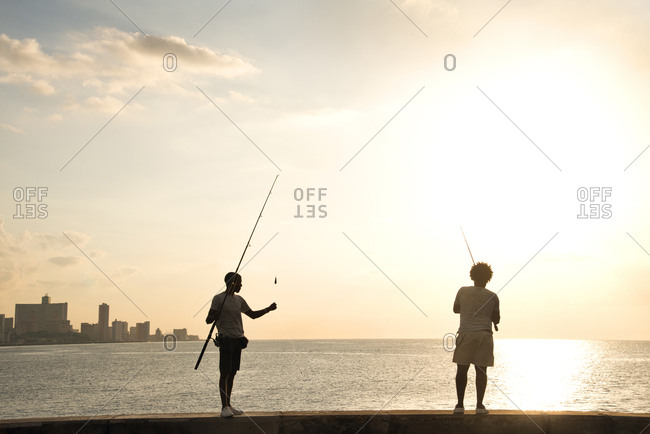 Havana, Cuba - May 23, 2017: Men fishing along a wall on the Malecon at sunset