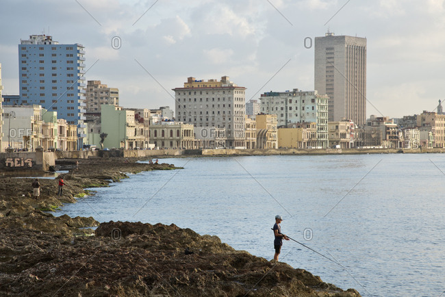 Havana, Cuba - May 23, 2017: People fishing from the shore along the Malecon at sunset