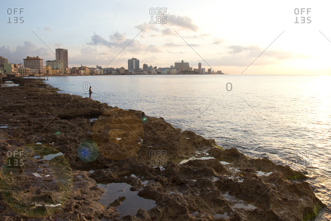 Havana, Cuba - May 23, 2017: Person fishing along the rocky shore of the Malecon at sunset