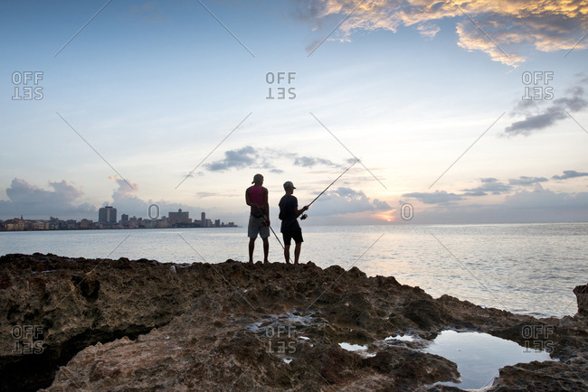 Havana, Cuba - May 23, 2017: Two men fishing from the rocky shore along the Malecon at sunset