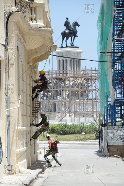Havana, Cuba - May 23, 2017: Men suspended by ropes working on the exterior of an historic building