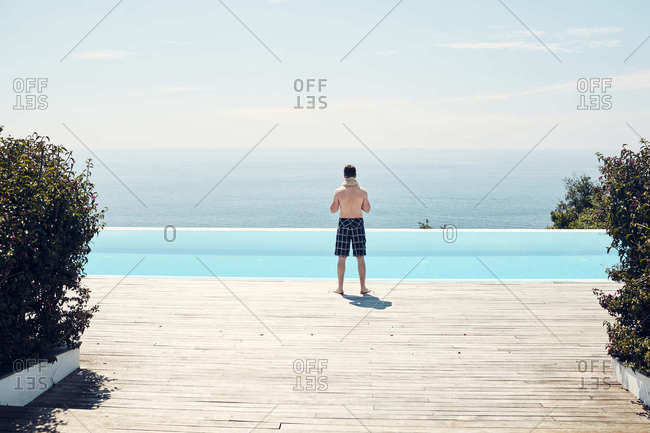 Man standing on edge of swimming pool overlooking the ocean