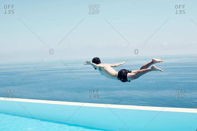 Man diving into swimming pool overlooking the ocean