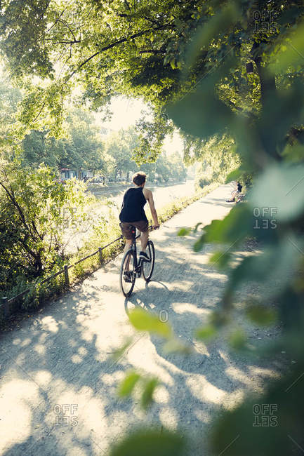 Man riding bike beside river in Berlin, Germany