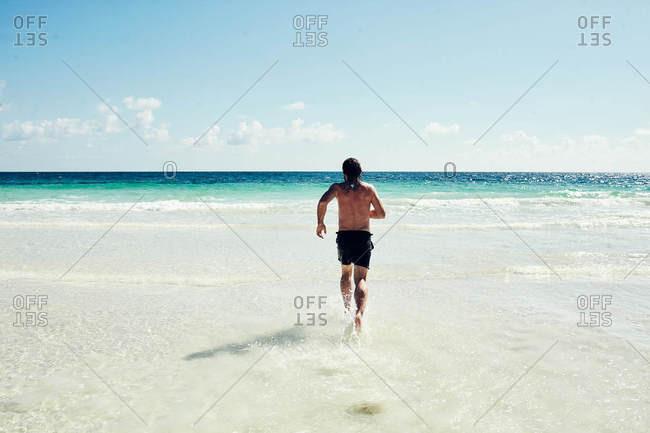 Man running towards waves on the coast of Tulum, Quintana Roo, Mexico