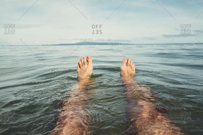 Man's feet floating in the ocean