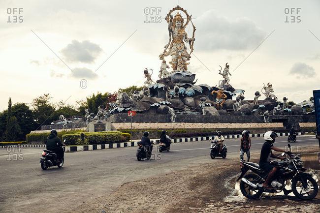 Denpasar, Bali, Indonesia - January 6, 2017: Motorcyclist riding by Patung Titi Banda