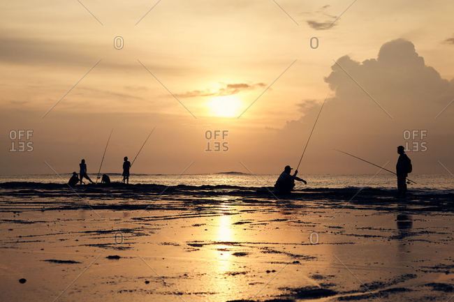 Silhouette of people fishing on the coast of Pulukan, Bali, Indonesia