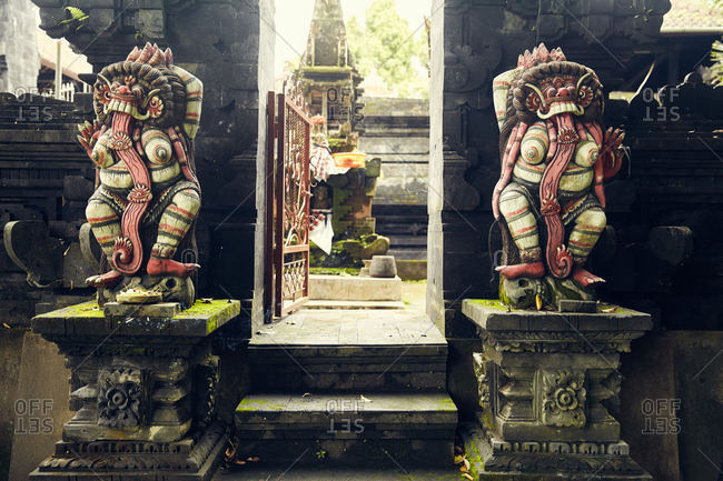 Colorful statues beside an open gate in Bali, Indonesia