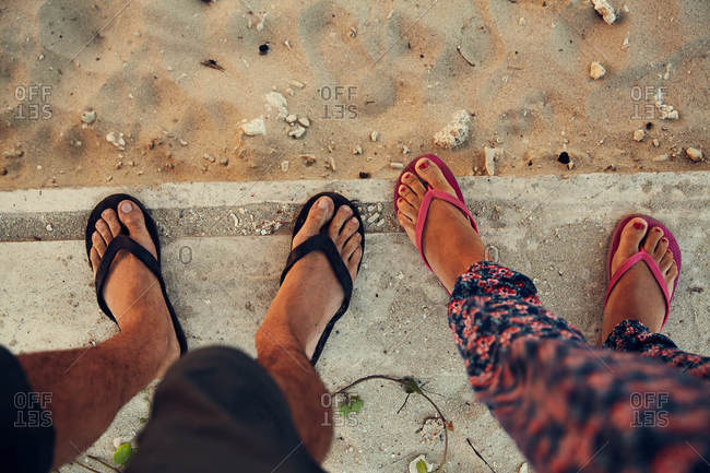Feet of two people by beach