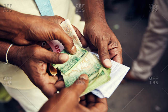 Men exchanging money, Sri Lanka