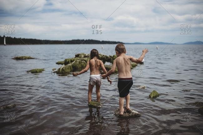 Girl and boy walking in ocean