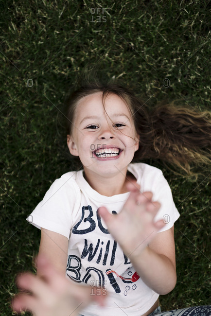 Girl laying in grass laughing