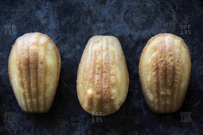 Three madeleines on dark background