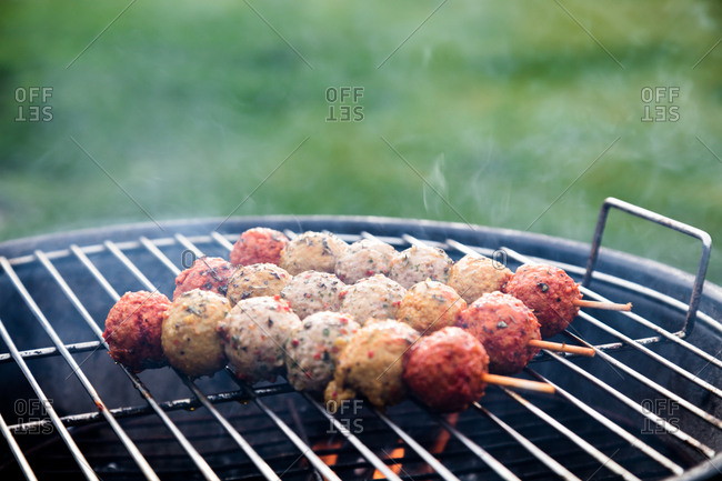 Meatball skewers roasting on a barbecue