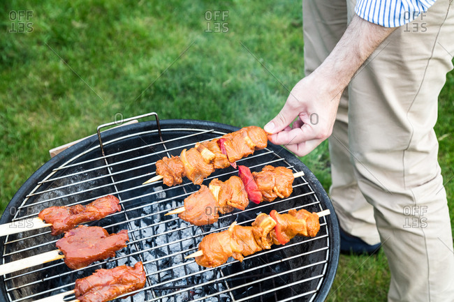 Man flipping skewers with his hands