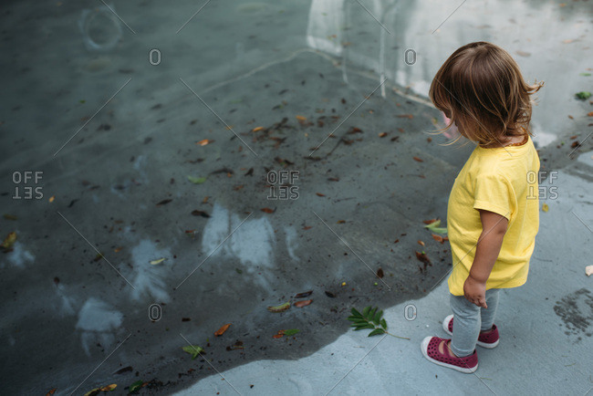 Toddler wearing yellow shirt looking into puddle
