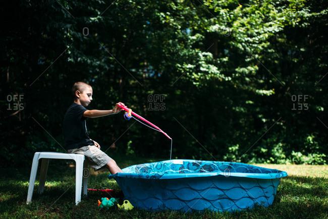 Boy pretending to fish in a kiddie pool