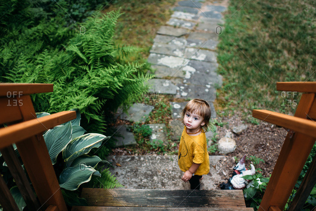 Toddler in yellow shirt standing at bottom of steps near stone path