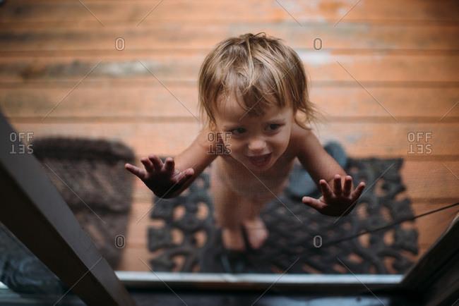 Toddler pressing hands against screen door