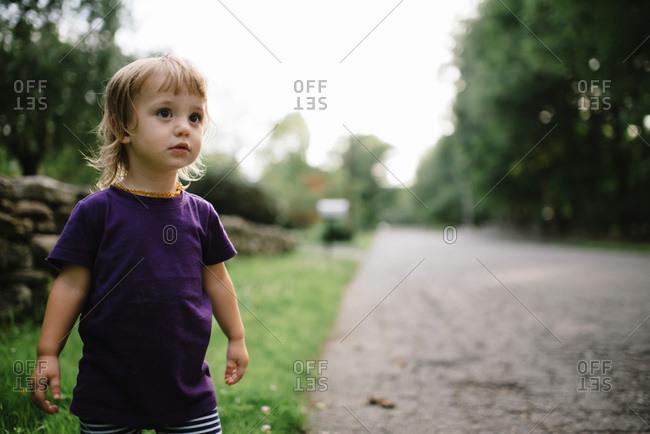 Toddler walking down a rural street