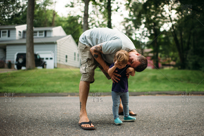Father bending down to kiss his toddler on a street