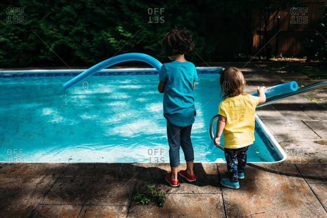 Sisters standing by a pool holding floats