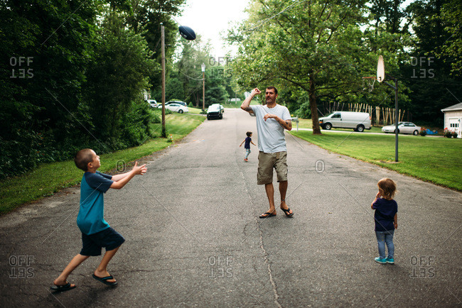Father and children playing catch on a suburban street