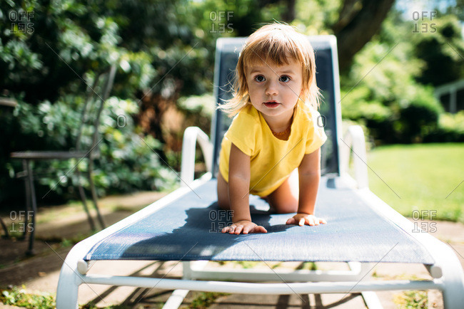 Toddler in yellow shirt climbing on blue lounge chair outside