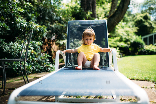 Toddler in yellow shirt sitting on blue lounge chair outside