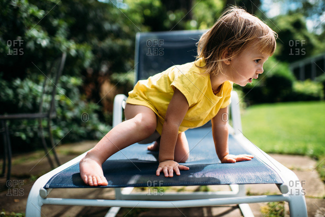 Toddler in yellow shirt sitting on blue lounge chair outside.