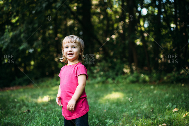 Happy toddler smiling at camera in front of trees