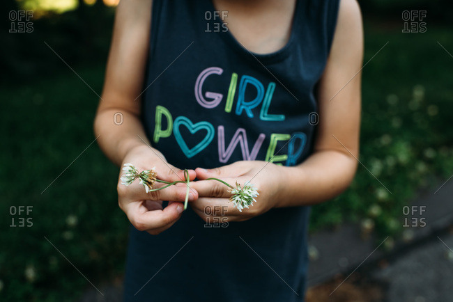 Close up image of girl's hands holding clover flowers