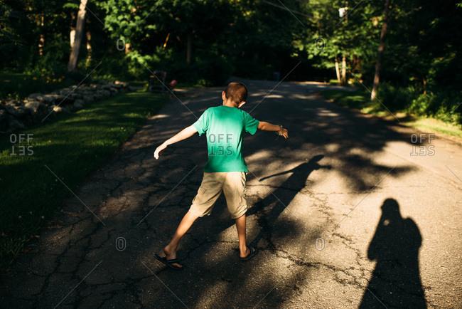 Boy walking down street making shadows