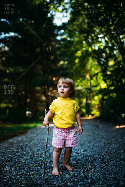 Toddler girl in gravel driveway holding stick