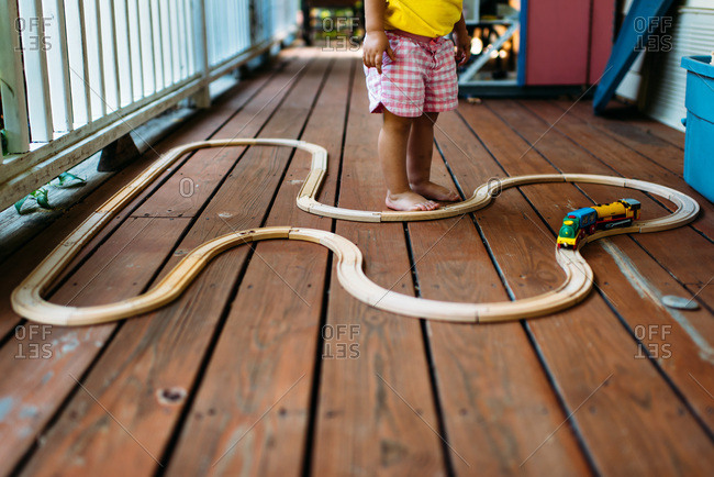 Toddler girl playing with trains and wooden tracks on a porch