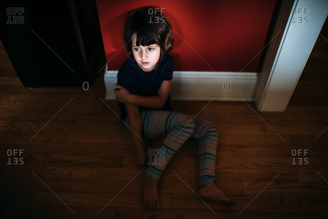 Young girl sitting against red wall