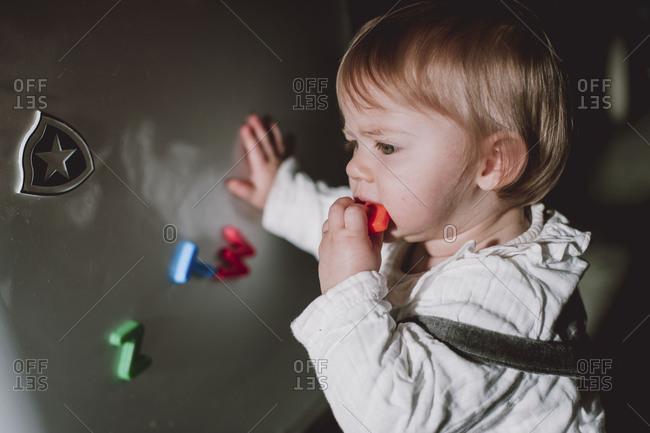 Little boy eating magnet letters