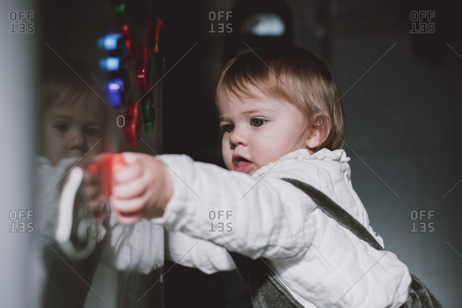 Baby playing with magnets on fridge