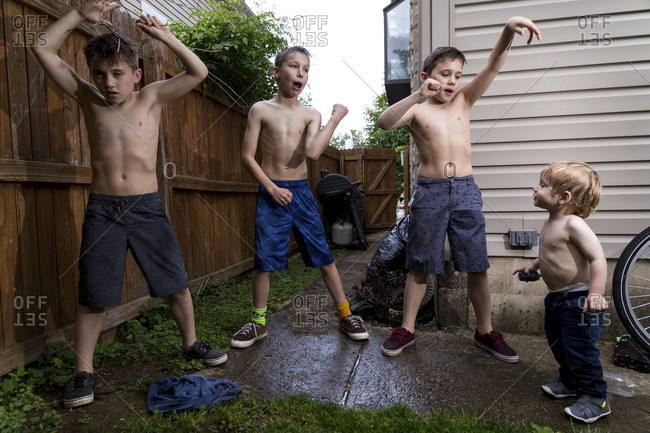 Four caucasian boys playing outside a home in Summer