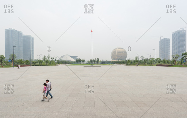 Two people walking in the almost empty new business district Qianjiang xin cheng (Qianjiang new city) near the river