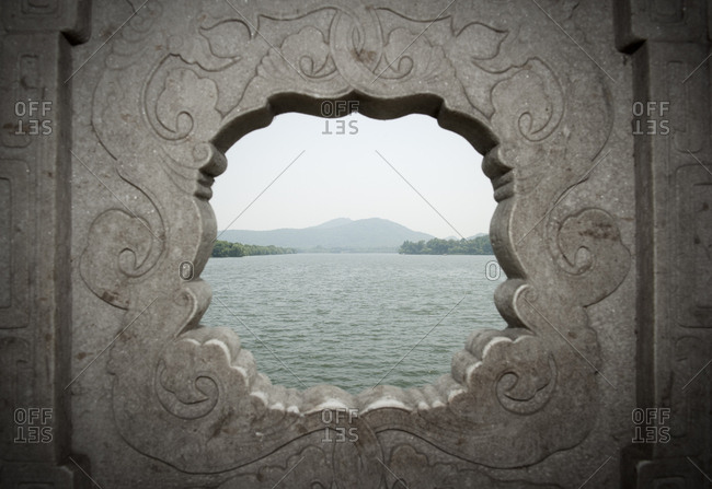 Looking out over the west lake and its shore through a hole on a bridge on the West Lake, the big tourist attraction of  Hangzhou in China