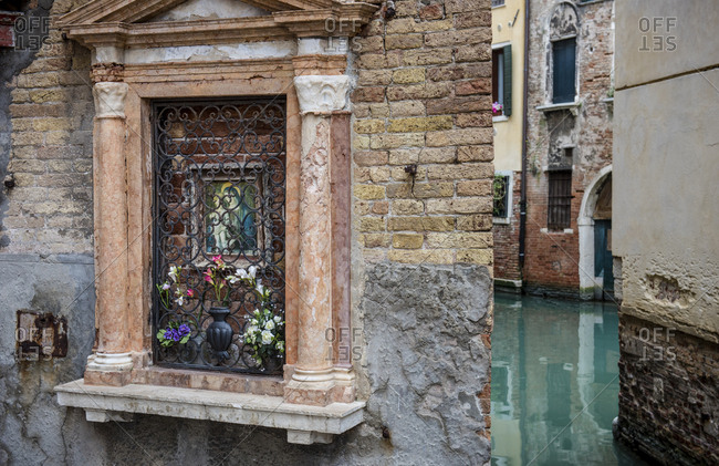 Small canal and a shrine with flowers and mary in Venice Italy