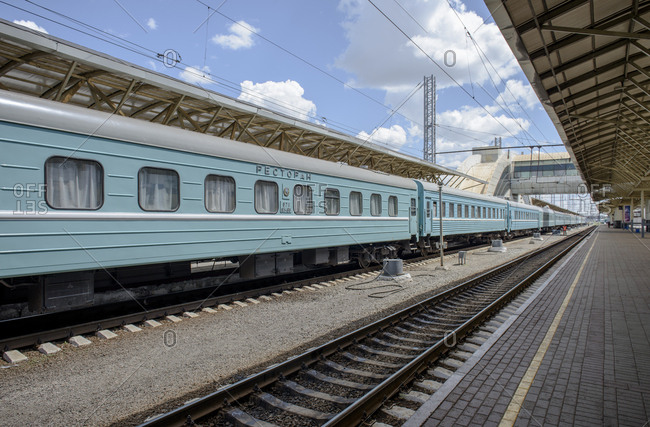 A blue Kazakh restaurant train and carriage waiting in the Astana railway station