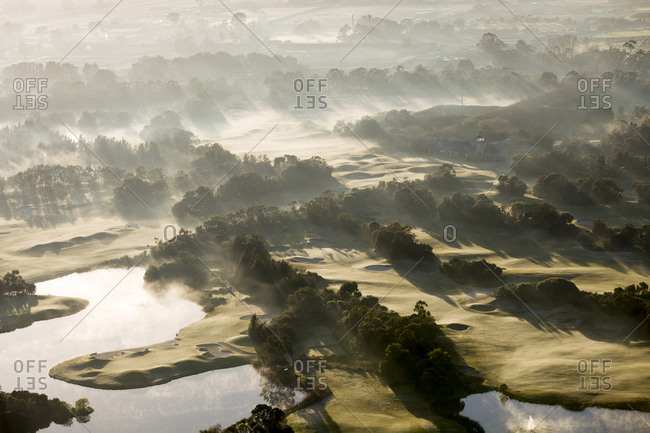 Morning sun shining on misty green hills and ponds on a golf course