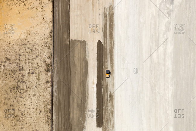 Industrial vehicle driving on a vast flat surface with striations
