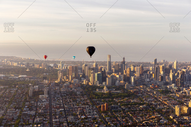 Melbourne, Australia - October 31, 2014: Hot air balloons floating over the city skyline at sunrise